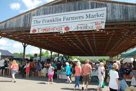 Picture of the franklin farmers market with people walking around, shopping in the warm sun