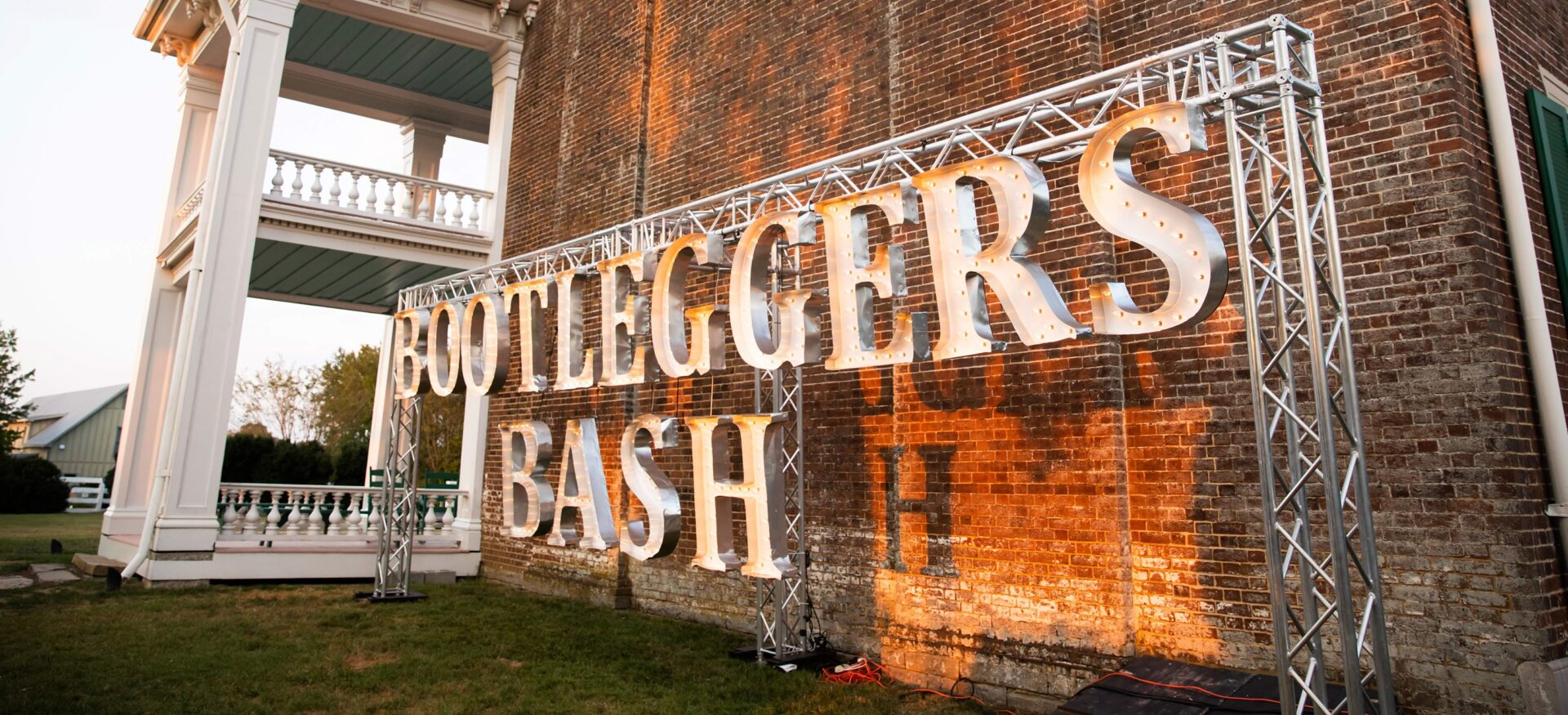 Bootlegger's Bash sign, an annual event in Franklin, TN featuring Tennessee distillers, a traditional Southern dinner and live entertainment featuring Rock & Roll Pianos – a dueling piano team.