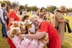 Girl hugging stick horses at Chukkers for Charity.
